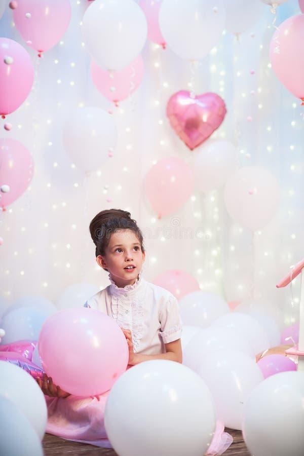 一个美丽的十几岁的女孩的画象一条豪华的桃红色裙子的在气球风景  箔和乳汁气球充满氦气 免版税库存图片