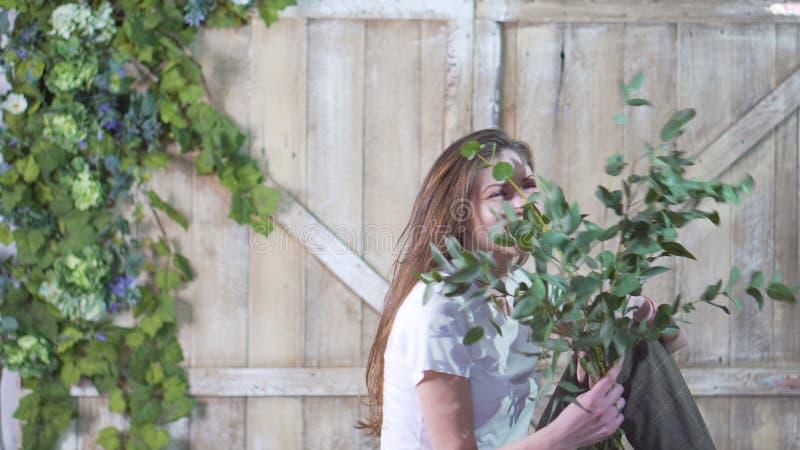 一个美丽的卖花人女孩的画象有一个玉树分支的反对用花装饰的一个木门 库存照片