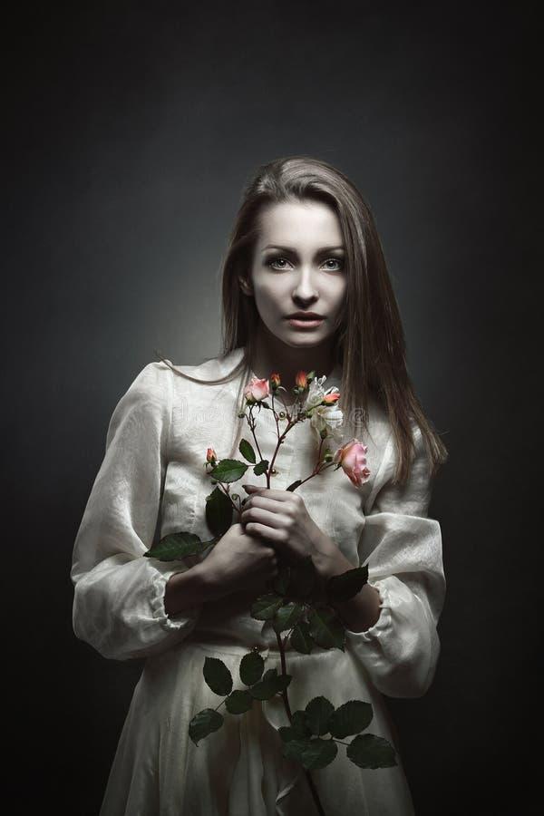 一个美丽的吸血鬼的画象有玫瑰花蕾的 免版税库存照片