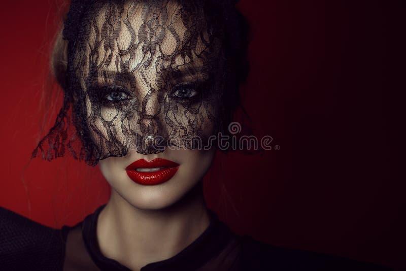 一个美丽的夫人的画象的关闭有生动的蓝眼睛的和完善做掩藏她的在鞋带黑色面纱后的面孔 免版税库存照片