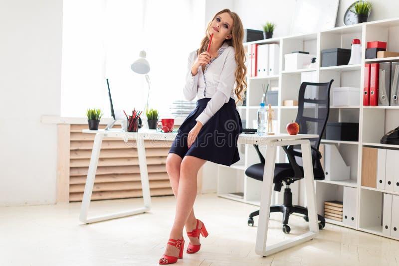 一个美丽的女孩在一张桌附近在她的手上站立在办公室并且拿着一支红色铅笔 库存图片