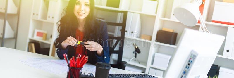 一个美丽的女孩在办公室在她的手上坐在桌上并且拿着一个黄色标志 免版税库存图片