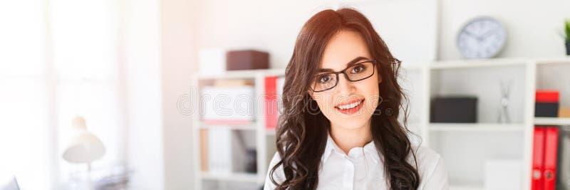 一个美丽的女孩在办公室桌,在她的胸口扣紧的手附近站立 免版税库存照片