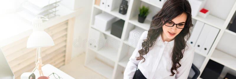 一个美丽的女孩在办公桌附近在她的手上站立并且拿着笔记和铅笔的板料 免版税库存图片
