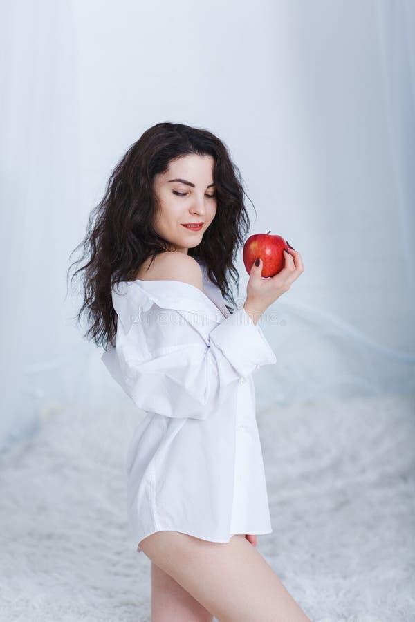 一个美丽的女孩在卧室站立,看得下来并且拿着一个红色苹果 图库摄影