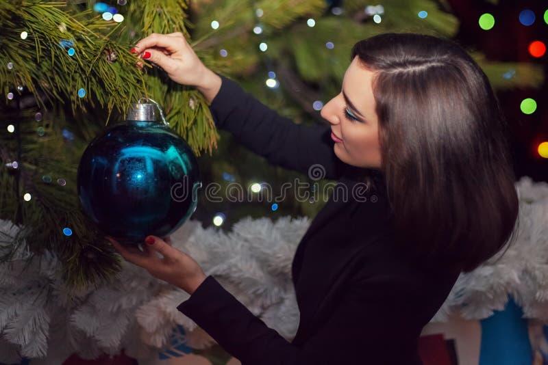一个美丽的女孩在圣诞树垂悬在Ne的一个大蓝色球 免版税库存照片