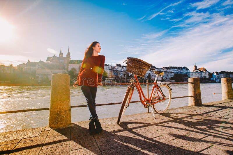 一个美丽的女孩在堤防在有红色篮子的一辆城市自行车附近在瑞士,市站立巴塞尔 晴朗 免版税库存照片