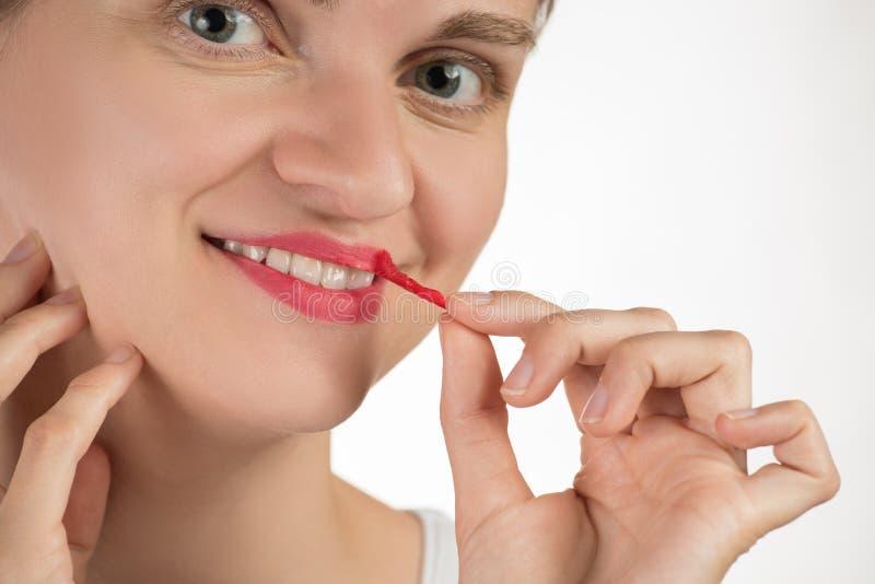 一个美丽的女孩应用一支坚持液体红色唇膏 免版税库存照片