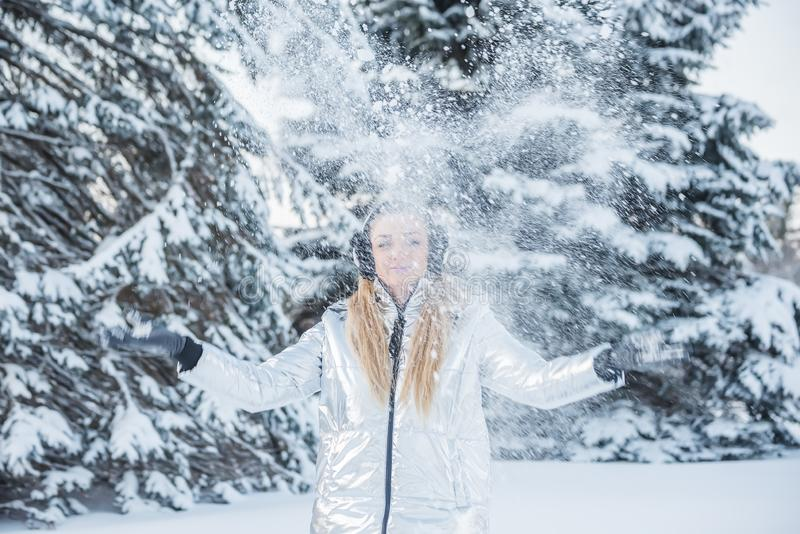 一个美丽的女孩投掷在一块森林沼地的雪在大树中 免版税库存图片