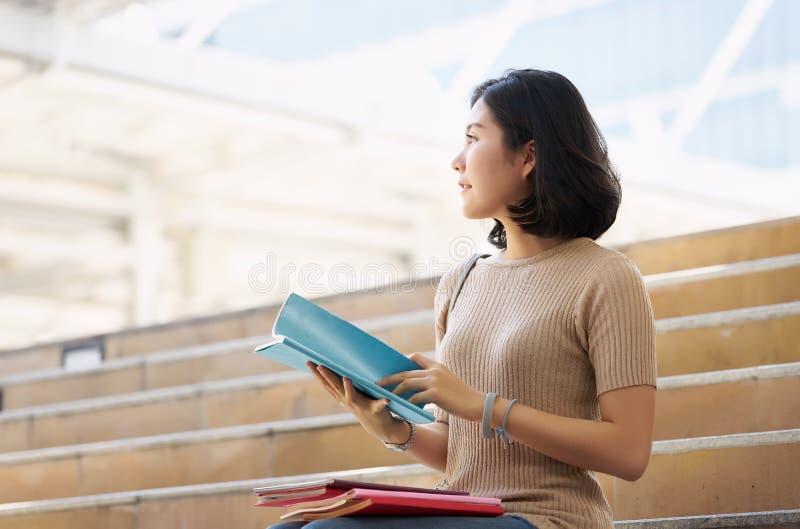 一个美丽的女孩的侧视图画象坐城市台阶 免版税库存图片