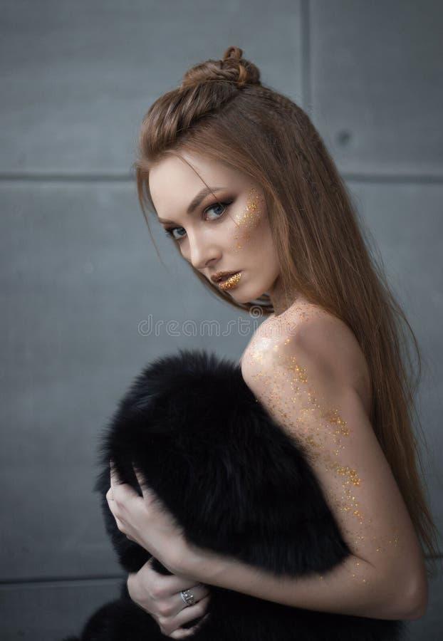 一个美丽的女孩的时兴的射击皮大衣的 免版税库存照片