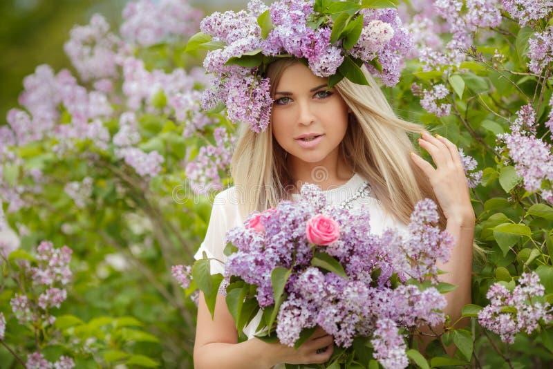 一个美丽的女孩的春天画象有丁香的 免版税图库摄影