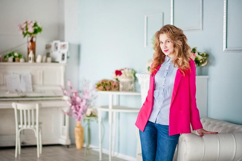 一个美丽的女孩的照片一件桃红色夹克和蓝色牛仔裤的在春天装饰了房子的内部 图库摄影