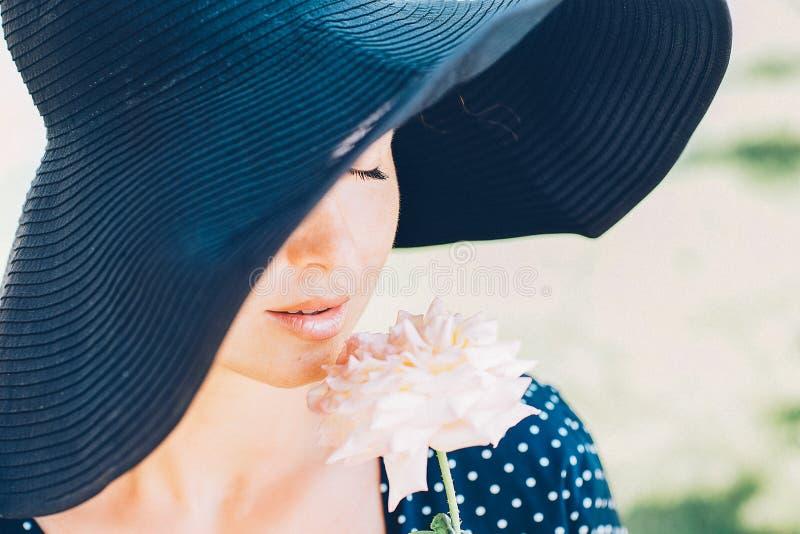 一个美丽的女孩的画象一个帽子和一朵玫瑰的在她的手上 图库摄影