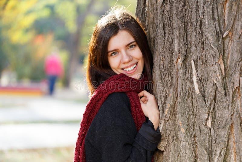 一个美丽的女孩的画象在一棵树附近的秋天公园在一条红色围巾,看照相机 免版税库存图片