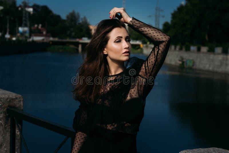 一个美丽的女孩的画象在街道上的在河附近的桥梁 性别 库存照片