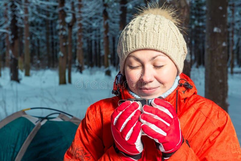 一个美丽的女孩的画象有一个杯子的热的茶在一个冬天f 免版税库存图片