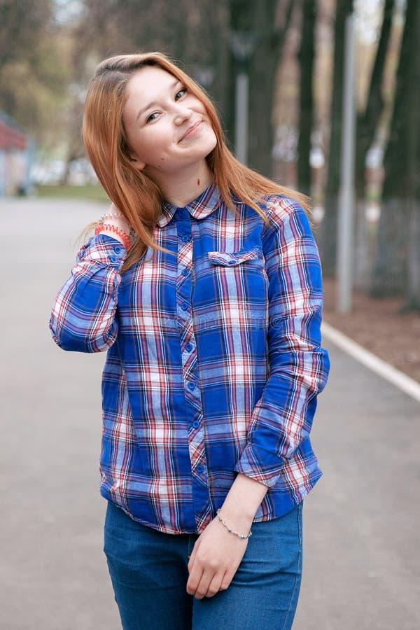 一个美丽的女孩的纵向 微笑,摆在照相机 在笼子的一件蓝色衬衣 以秋天为背景 免版税库存照片