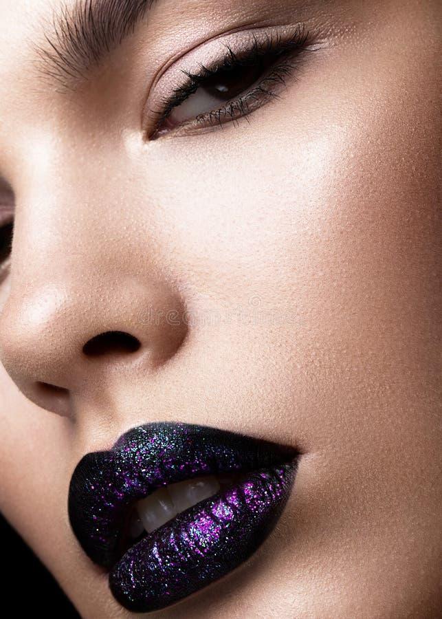 一个美丽的女孩的纵向 精采光滑的嘴唇特写镜头 在黑唇膏的紫色闪烁 免版税库存照片