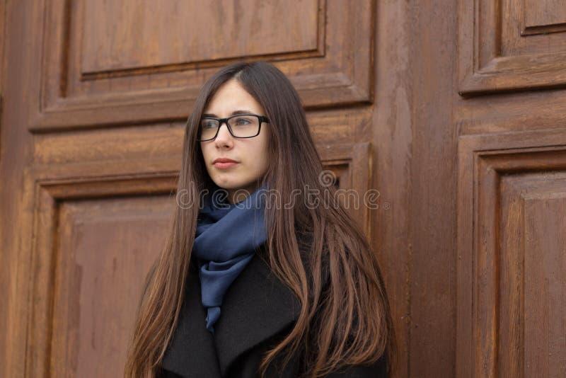 一个美丽的女孩的画象一个大木门的背景的 免版税库存图片