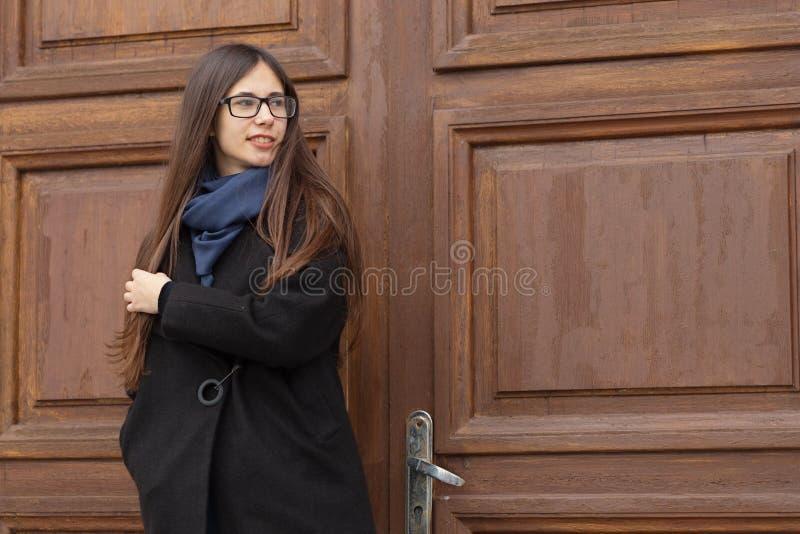 一个美丽的女孩的画象一个大木门的背景的 免版税图库摄影