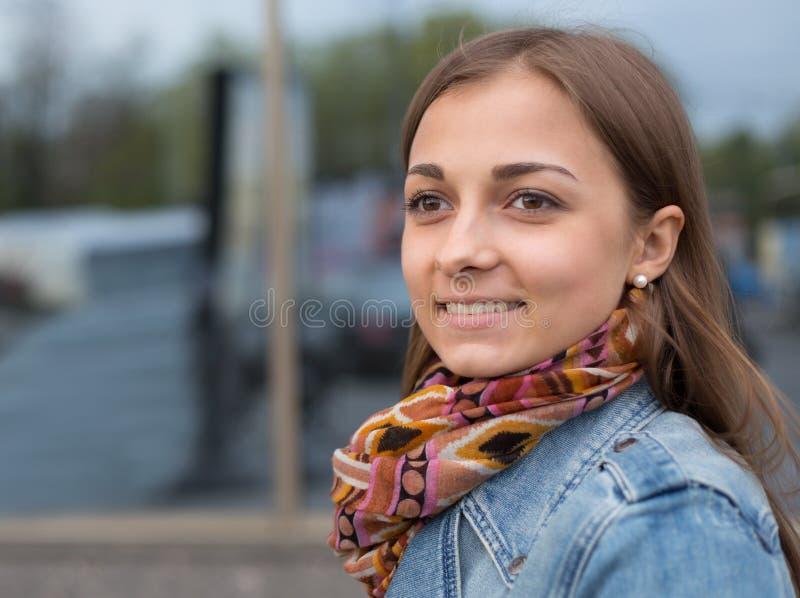 一个美丽的女孩的画象一件牛仔布夹克的有围巾的 库存图片