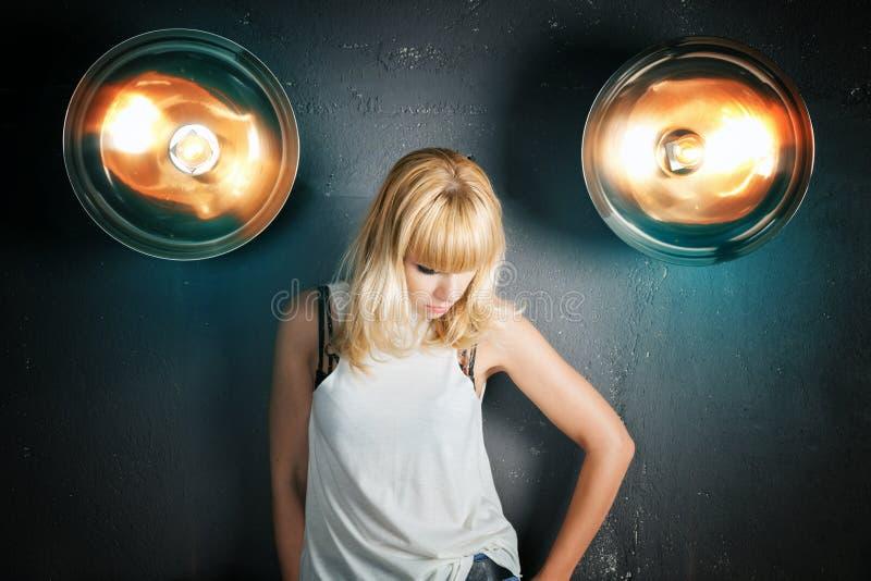 一个美丽的女孩的画象反对墙壁背景的  免版税库存图片