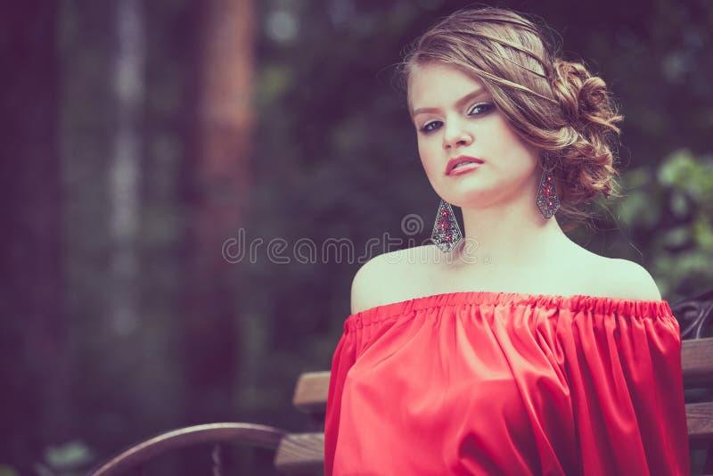 一个美丽的女孩的画象户外一件红色礼服的 免版税图库摄影