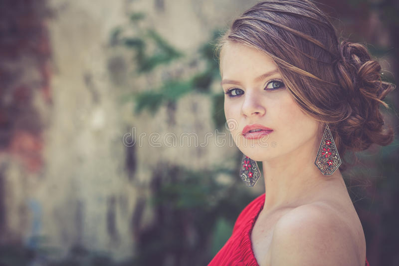 一个美丽的女孩的画象户外一件红色礼服的 库存照片