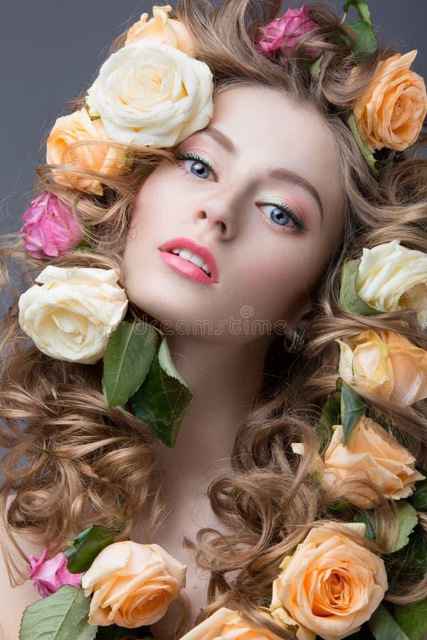 一个美丽的女孩的画象有柔和的桃红色构成和许多的在她的头发的花 秀丽表面 图库摄影