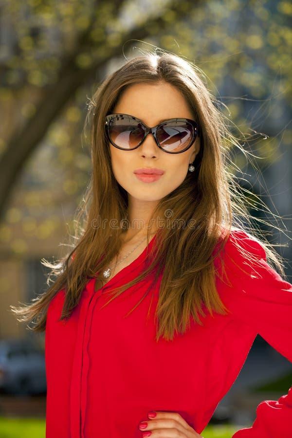 一个美丽的女孩的画象红色衬衣的在backgroun 免版税库存照片