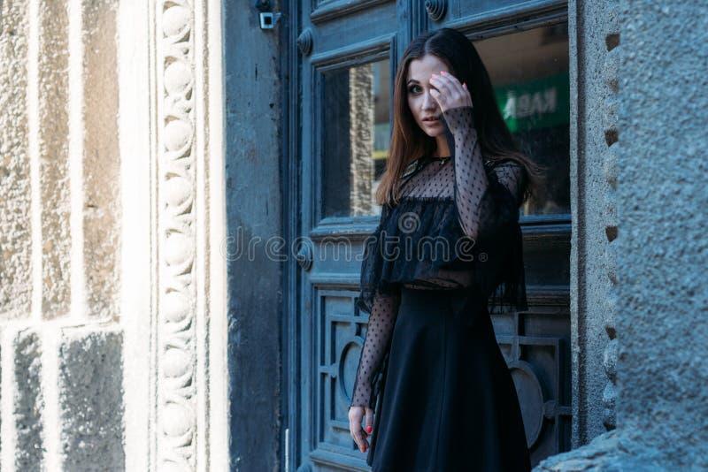 一个美丽的女孩,一件黑礼服的一个深色的女孩,在一个大黑门附近的立场的画象,进入它 一个新的阶段 免版税库存图片