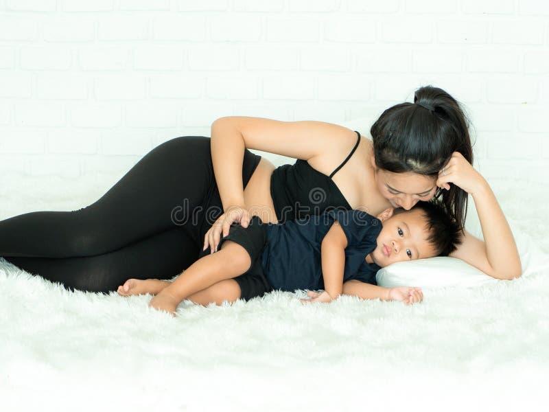 一个美丽的孕妇,躺在床上,高兴地照顾儿子 免版税库存图片