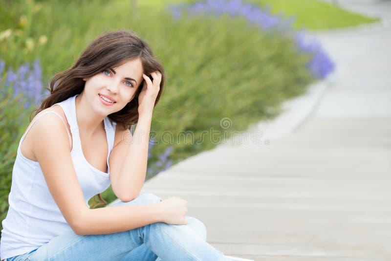 一个美丽的学生女孩的画象在公园 库存图片
