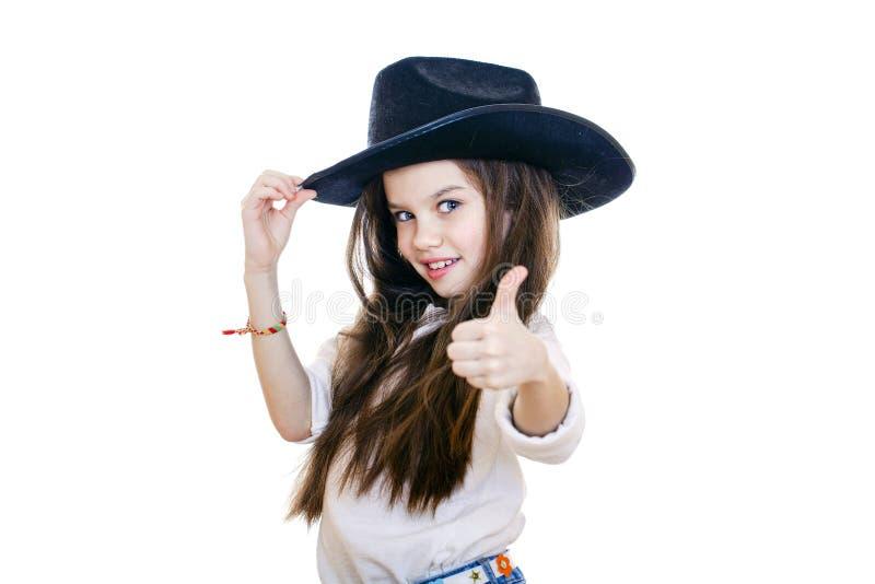 一个美丽的小女孩的画象一个黑牛仔帽的 免版税库存照片