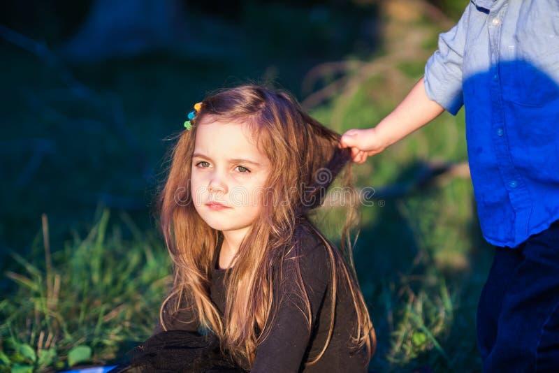 一个美丽的小女孩的画象,当她的小孩兄弟拉扯她的头发时 库存照片