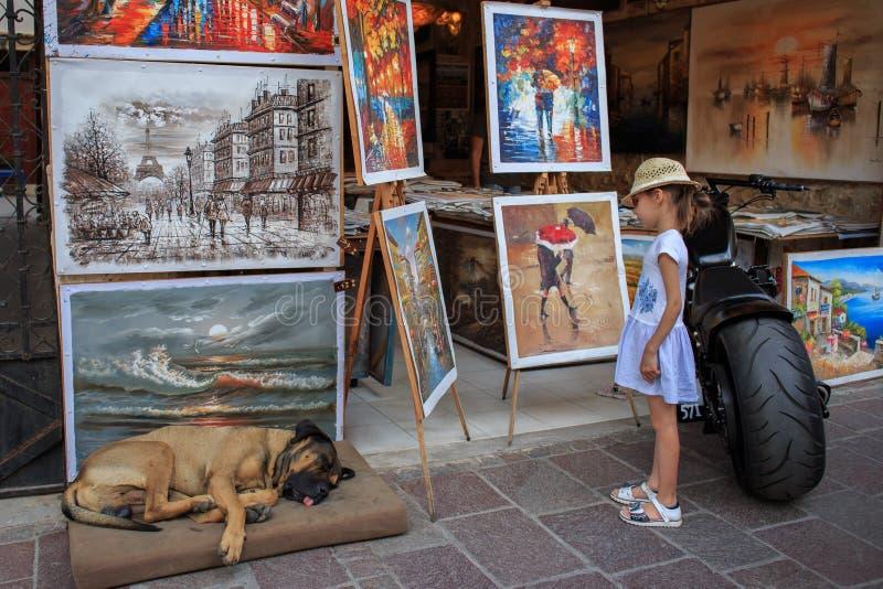 一个美丽的小女孩看绘画街道商店 库存照片