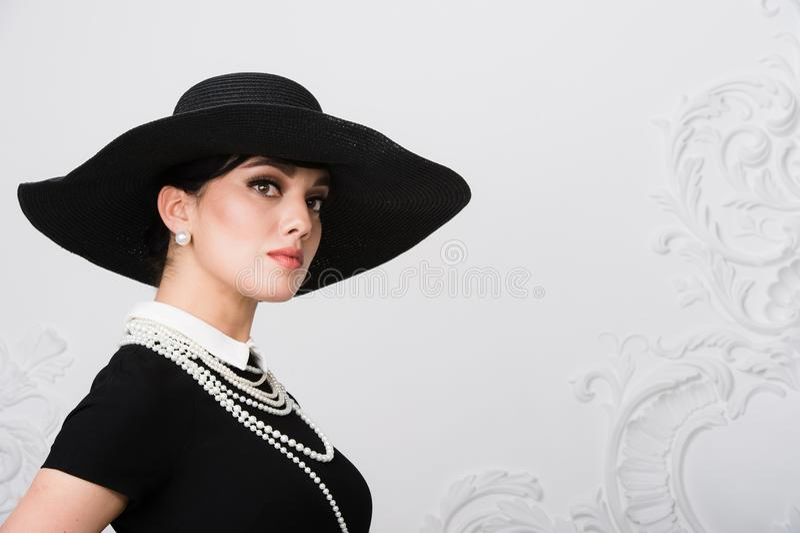 一个美丽的少妇的画象减速火箭的样式的在一件典雅的黑帽会议和礼服在豪华洛可可式的墙壁背景 免版税库存图片