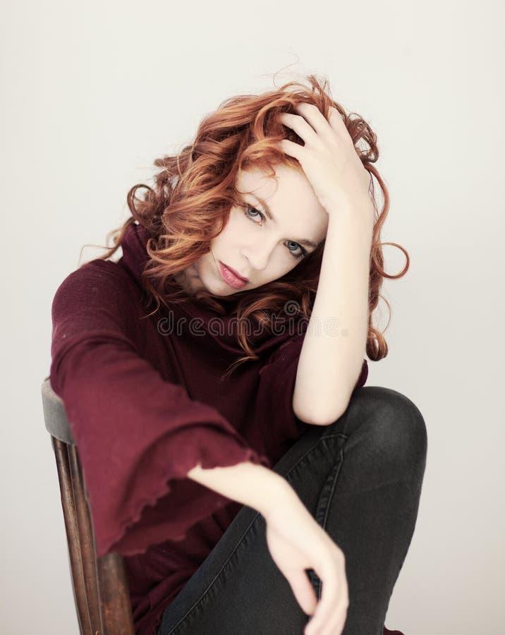 一个美丽的少妇的画象有长的红色卷发的和完善组成,舒适红色冬天毛线衣 免版税库存照片