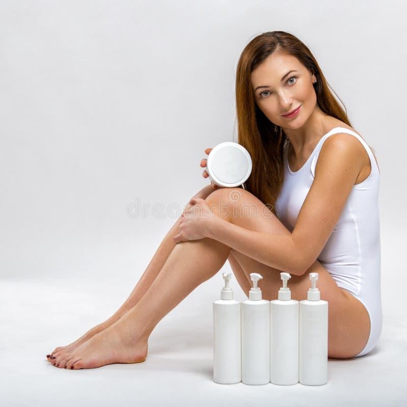 一个美丽的少妇的画象白色游泳衣的有润肤膏的在她的手上 机体关心英尺健康温泉水妇女 免版税库存照片