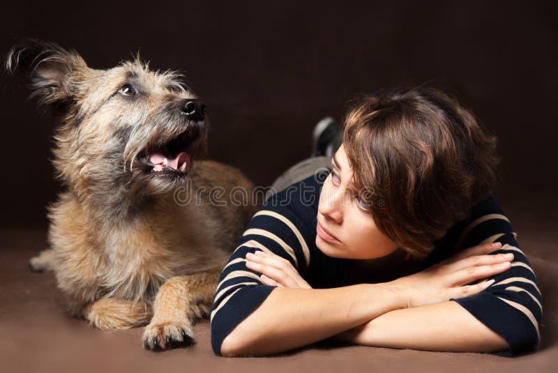 一个美丽的少妇的画象有一只滑稽的卷毛狗的在a 图库摄影