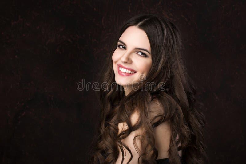 一个美丽的少妇的画象有健康长的头发和美好的微笑的在黑暗的背景 免版税库存照片
