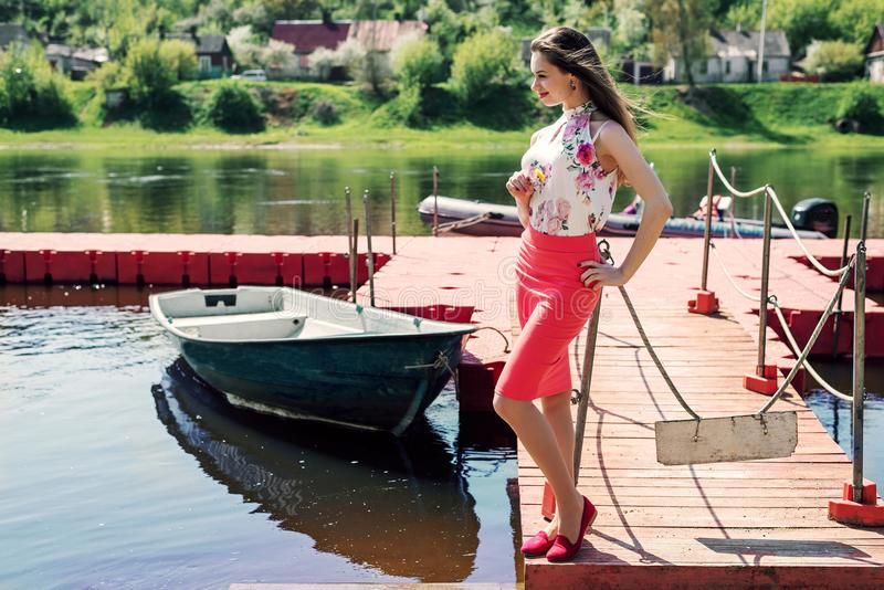 一个美丽的少妇穿戴了在码头的立场 免版税库存照片