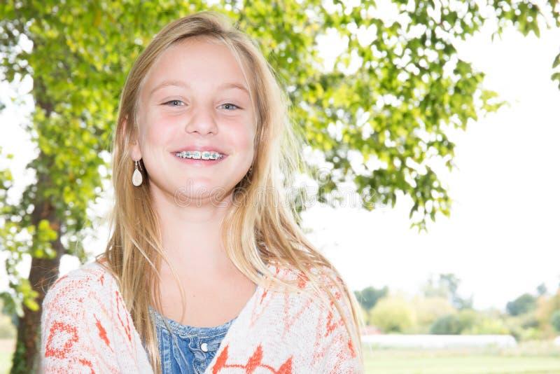 一个美丽的少年白肤金发的女孩的面孔有牙齿括号的 免版税库存照片