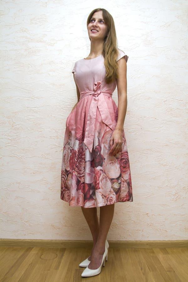 一个美丽的年轻愉快的确信的女孩的全长画象有摆在有桃红色花卉设计的夏天礼服的长的金发的 库存图片