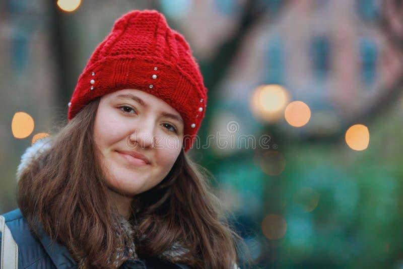 一个美丽的微笑的女孩的接近的画象有棕色头发五颜六色的光bokeh的 库存图片
