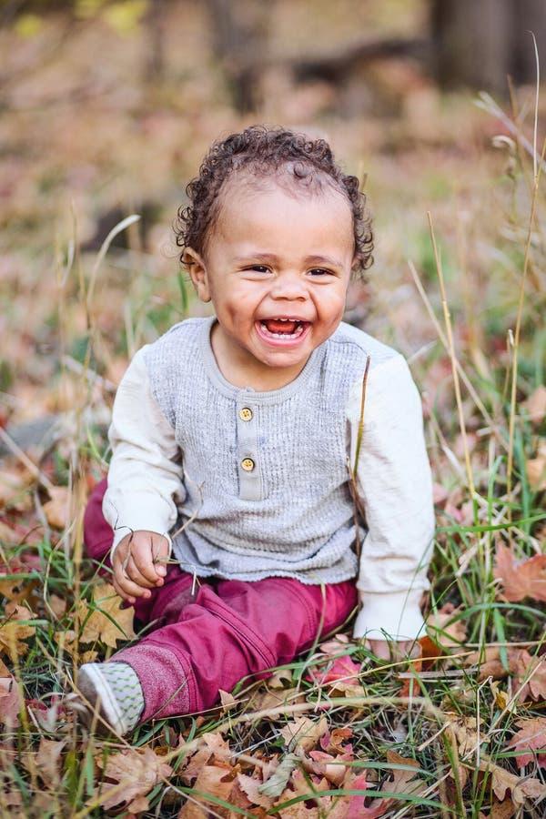 一个美丽的微笑的混合的族种小男孩的室外画象 免版税库存照片