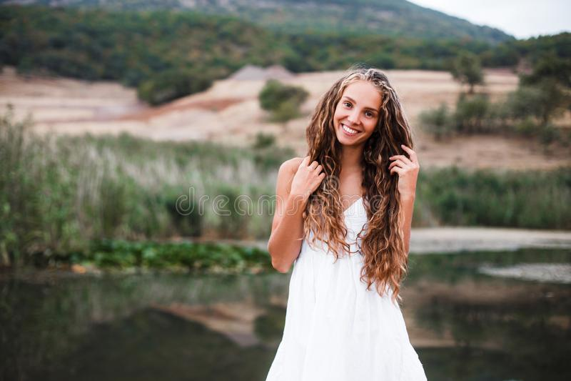 一个美丽的微笑的白肤金发的女孩的特写镜头画象有自然卷毛的 库存照片