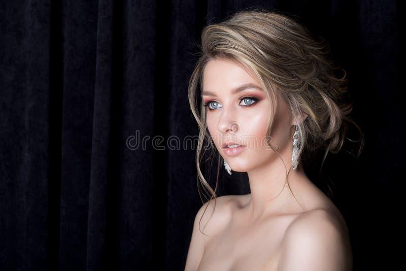 一个美丽的性感的逗人喜爱的女孩与光秃的肩膀o的新娘和构成的画象有一根美丽的婚礼晚上头发的 免版税图库摄影