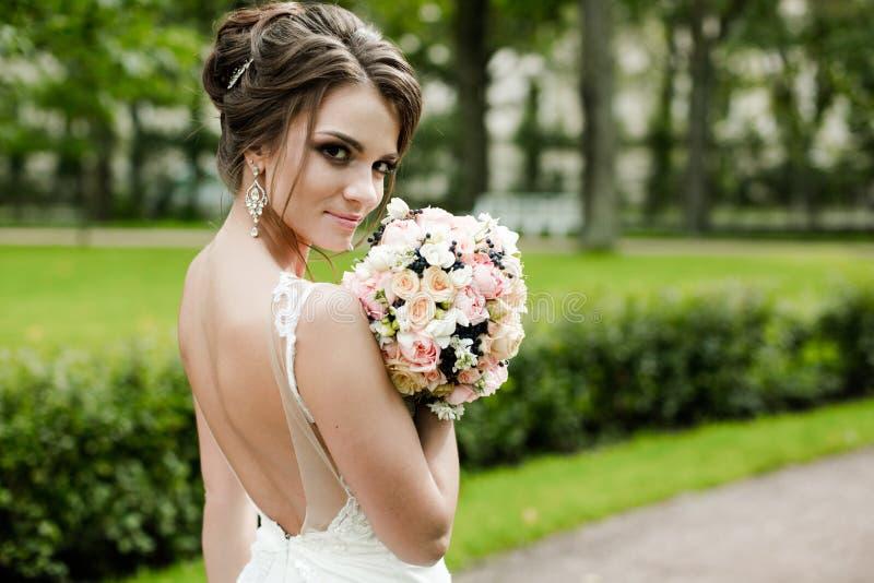 一个美丽的愉快的深色的新娘的画象握在花花束的婚姻的白色礼服的手户外 免版税库存图片